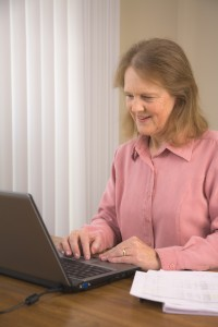 mature woman telecommuting using computer in home office
