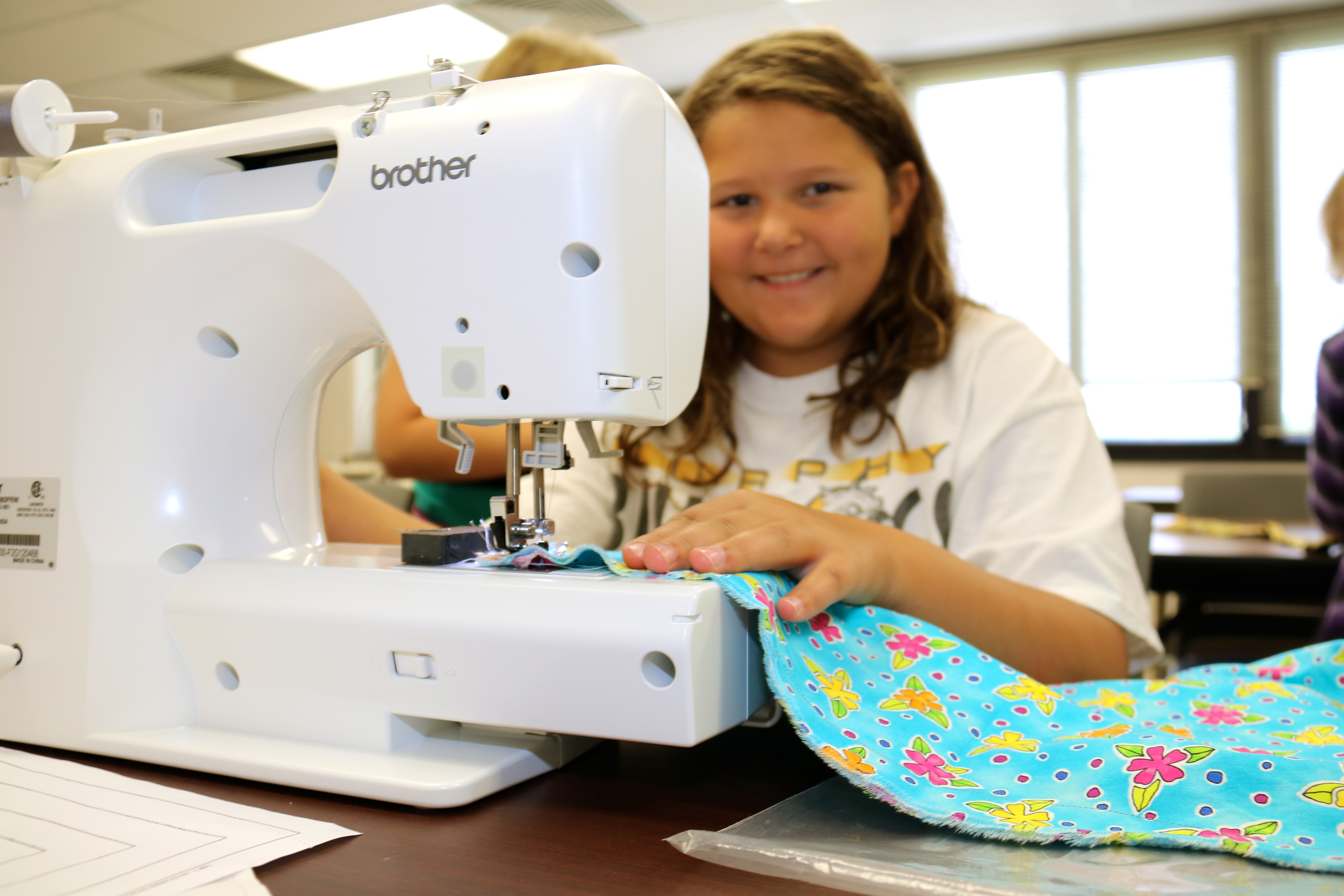 Emma Kephart practices sewing as part of the 2015 Kids College camps at Tri-County Community College.