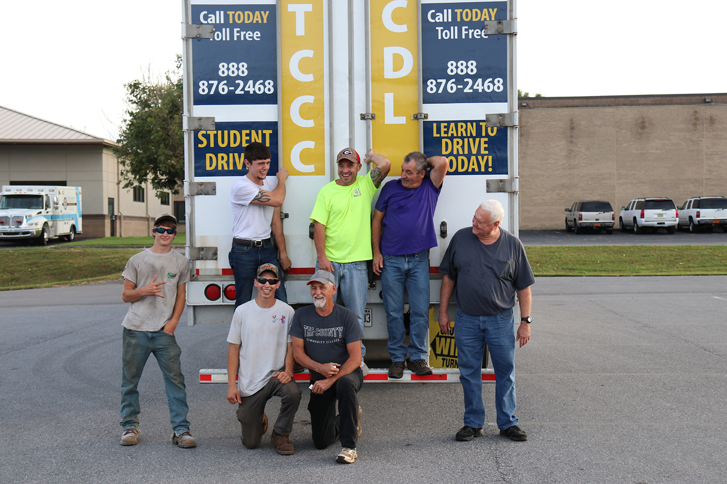 Tri-County Community College commercial driver license students (from left) Matthew Cody, Jesse Rogers, Nathaniel Cody, Arjuna King, John Olszewski, and Frank Barger pose with instructor Barry Helton (bottom center) in front of the college's new tractor-trailer at the main campus.