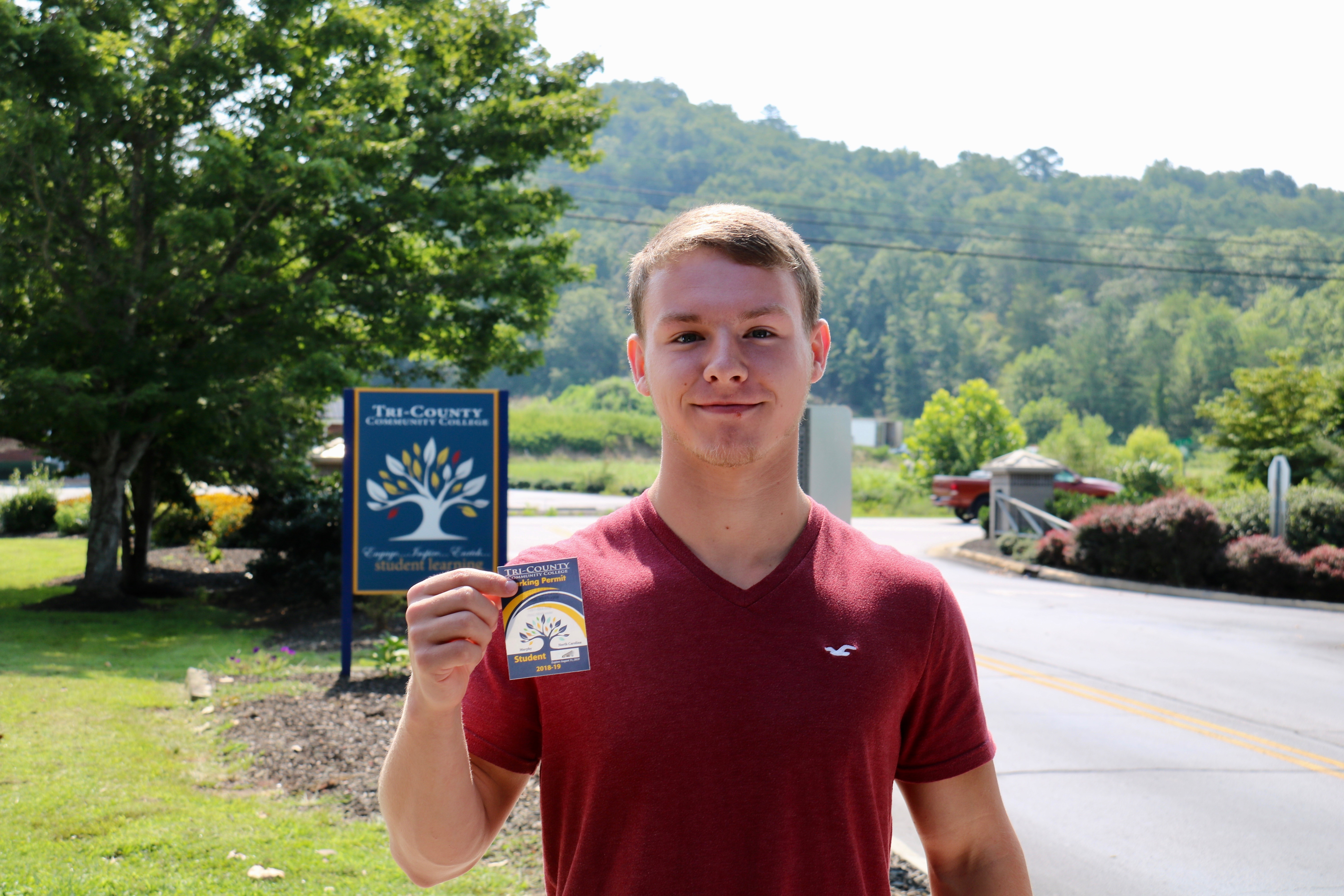 Evan Dillard, Tri-County Community College student, shows off his new college parking pass during fall registration last August at the main campus in Peachtree.