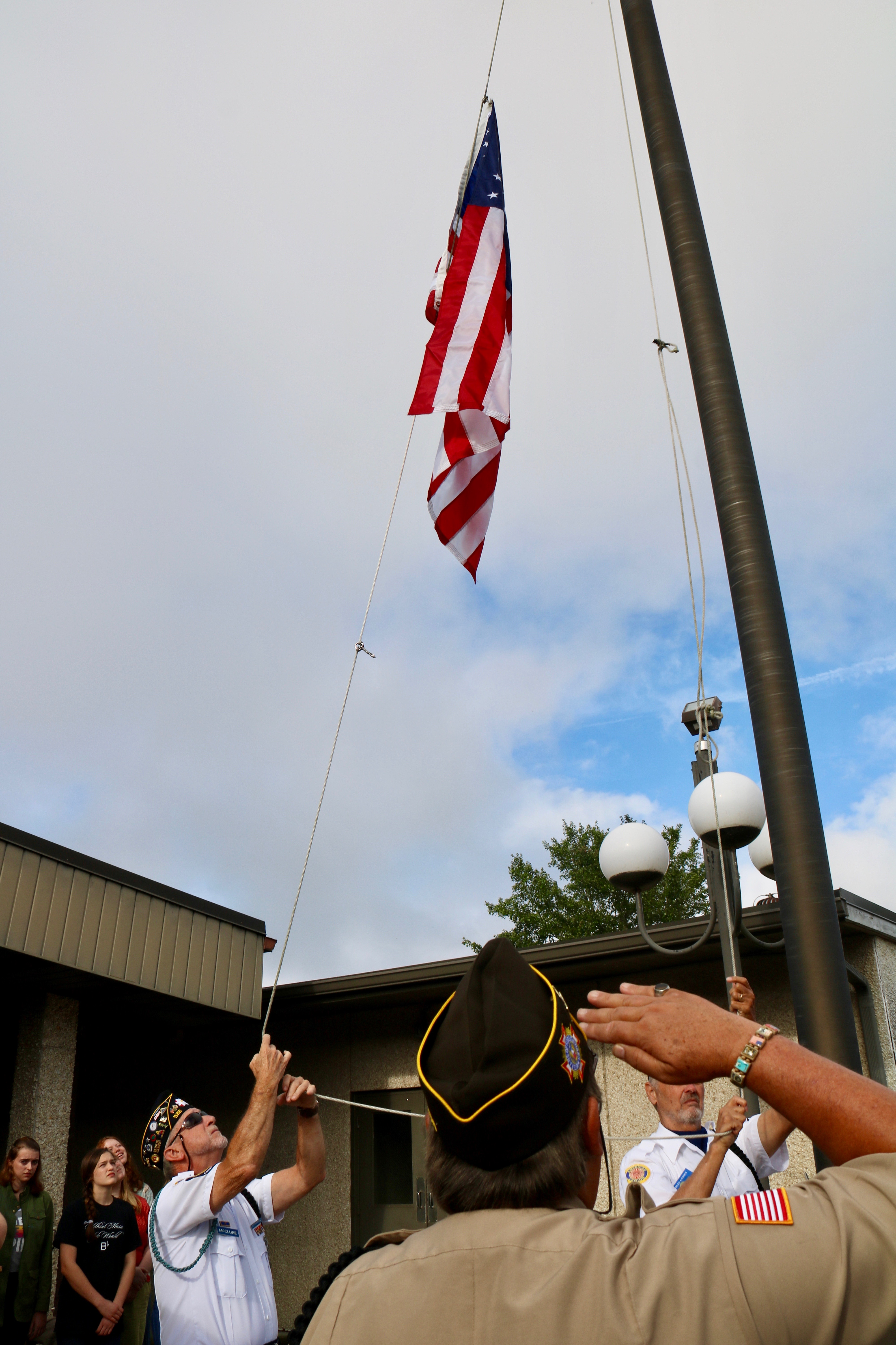 Dwight McClure, member of American Legion Post 532 in Hayesville, works to hoist an American flag at Tri-County Community College's annual Patriot Day ceremony on Sept. 11, 2018.